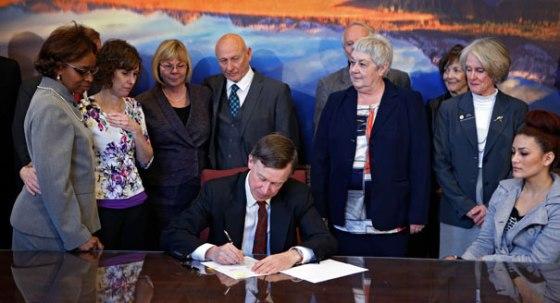 Governor John Hickenlooper (D-CO) signs a controversial gun control bill.